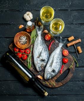 Сырая морская рыба дорадо с бокалами белого вина на черном деревенском столе