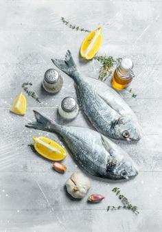 Сырая морская рыба дорадо с травами и специями. на деревенском фоне.