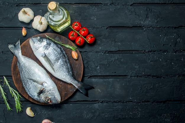 Сырая морская рыба дорадо с приправами и помидорами. на черном деревенском.