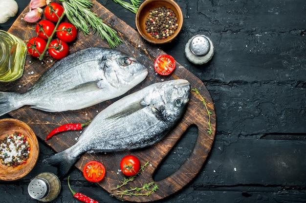 スパイスとローズマリーを添えた生の海魚ドラド。黒の素朴な背景に。