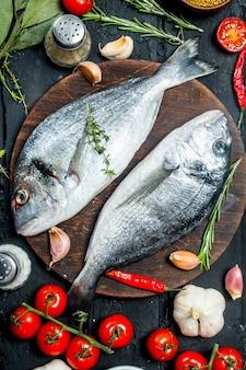 Сырая морская рыба дорадо со специями и овощами. на черном деревенском фоне.