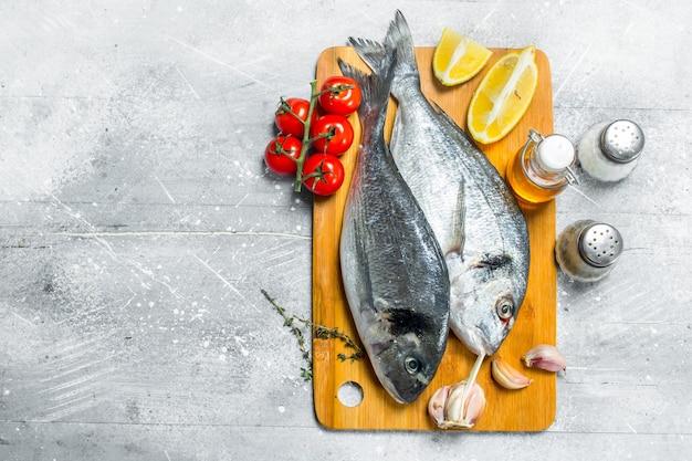 Сырая морская рыба дорадо с помидорами, дольками лимона и специями. на деревенском фоне.