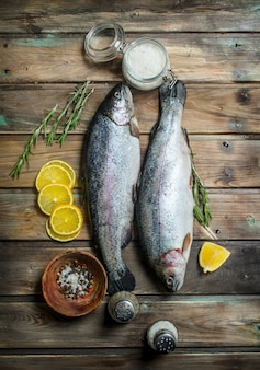 Лосось сырой морской рыбы с лимоном и специями. на деревянном фоне.