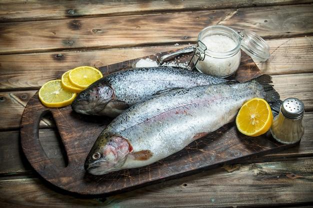 Сырая морская рыба с лимоном и специями. на деревянном фоне