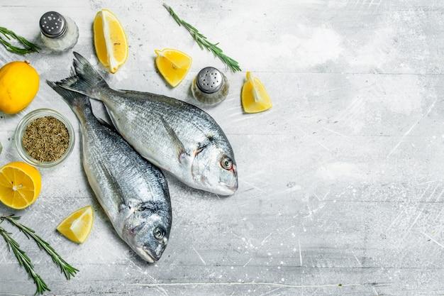 レモンウェッジとニンニクを添えた生の海の魚。素朴な背景に。