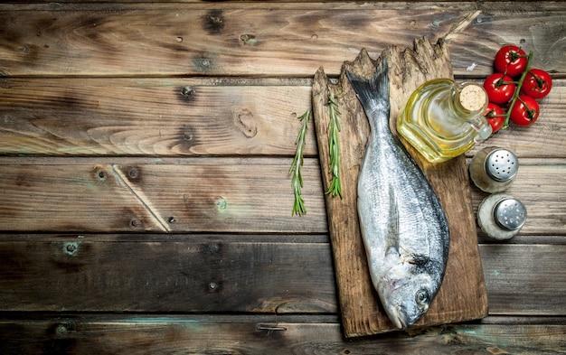 Сырая морская рыба с помидорами и зеленью. на деревянном фоне.