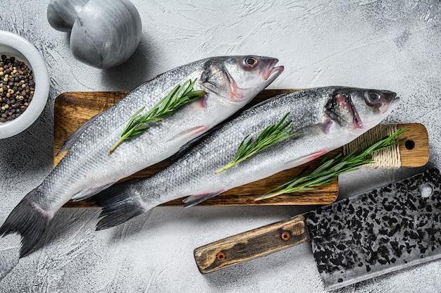 スパイス、ハーブとまな板の上で生のシーバス魚。白色の背景。上面図。