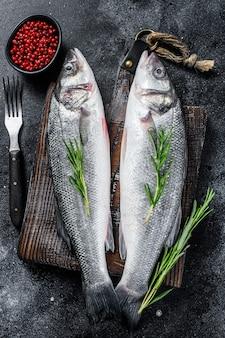 향신료, 허브와 함께 커팅 보드에 원시 seabass 물고기.
