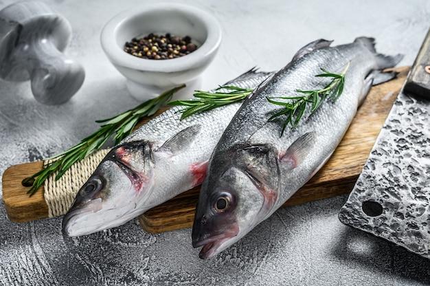 Сырая рыба морского окуня на разделочной доске со специями, зеленью.