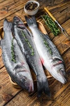 Сырая рыба морского окуня на подносе. деревянный фон. вид сверху.