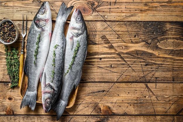 Сырая рыба морского окуня на подносе.