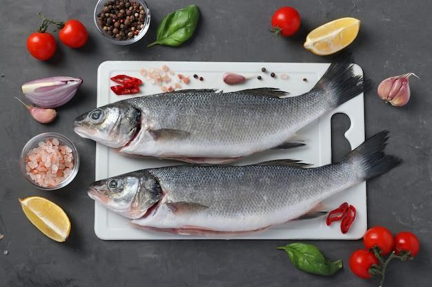 어두운 배경에 흰색 플라스틱 보드에 바질, 레몬, 소금, 후추, 체리 토마토, 마늘과 같은 재료와 조미료를 넣은 생 농어. 위에서 보기