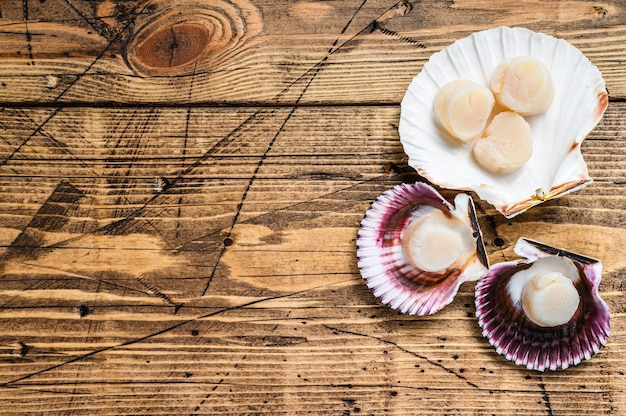 木製のテーブルの殻に生のシーフードホタテの肉。上面図。