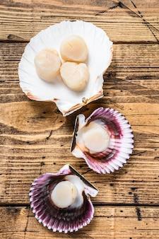 Мясо гребешков сырых морепродуктов на раковинах. деревянный фон. вид сверху.