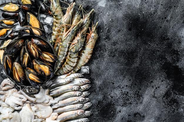 Сырые морепродукты, тигровые креветки, креветки, голубые мидии, осьминоги, сардины, корюшка. вид сверху. скопируйте пространство.
