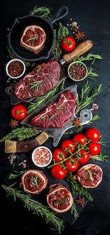 Сырые стейки говядины на более мясном ноже мясника с темным фоном специй. закройте вертикальное изображение, место для текста.
