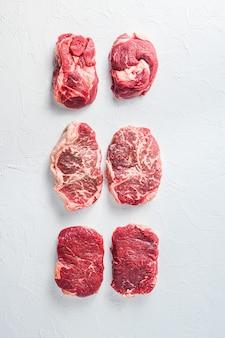 Необработанный набор альтернативных отрубов из говядины закатанный глаз, верхнее лезвие, стейк из огузка. органическое мясо. вид сверху.