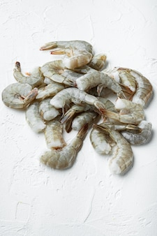 Raw shell on king prawns set, on white stone  surface, with copy space for text