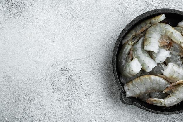 Сырая ракушка на королевских креветках, в чугунной сковороде, на сером каменном столе, плоская планировка, вид сверху