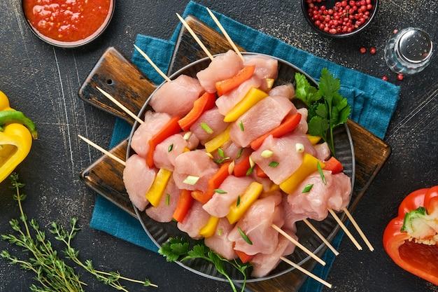 어두운 회색 배경에 나무 판자, 향신료, 허브, 야채에 있는 생 시시 케밥. 굴라시나 시시 케밥을 위한 바베큐 원시 재료. 평면도. 무료 복사 공간입니다.