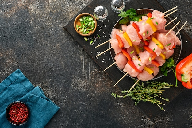 Raw shish kebab on wooden board, spices, herbs and vegetables on dark grey background. barbecue raw ingredients for goulash or shish kebab. top view. free copy space.
