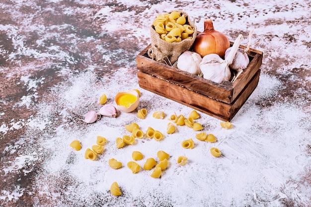 Сырые короткие макароны с луком и чесноком в мешковине на деревянной поверхности.