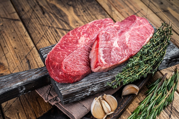 ハーブ入りの木製肉屋ボードに生のショルダートップブレードビーフミートステーキ。木製の背景。上面図。
