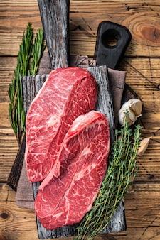 ハーブ入りの木製肉屋ボードに生のショルダートップブレードビーフミートステーキ。木製のテーブル。上面図。