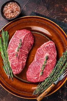 Raw shoulder top blade 컷 또는 호주 와규 굴 칼날 쇠고기 스테이크. 어두운 배경입니다. 평면도