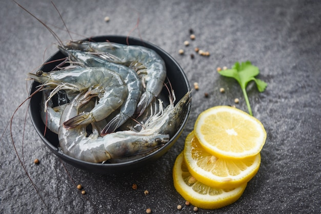 Raw shrimps on bowl - fresh shrimp prawns for cooking with spices lemon and celery