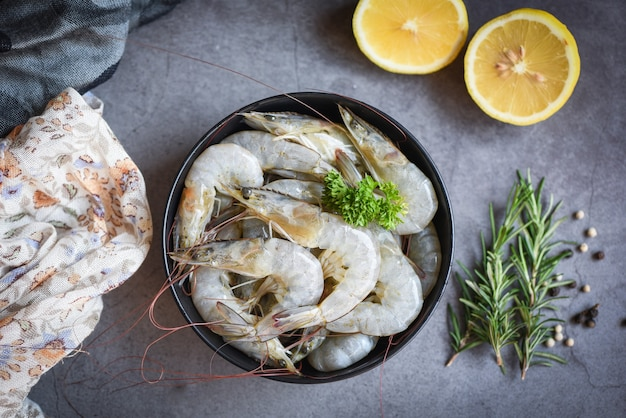 Raw shrimps on bowl with lemon and rosemary