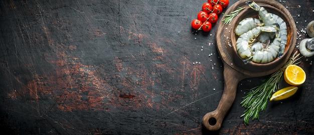 Сырые креветки в тарелке на разделочной доске с помидорами черри, розмарином и разрезанным лимоном.