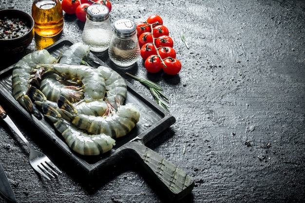 Сырые креветки на разделочной доске с помидорами черри и специями. на черном деревенском