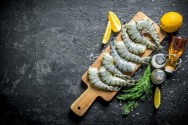 Сырые креветки на разделочной доске с дольками лимона, специями и укропом.
