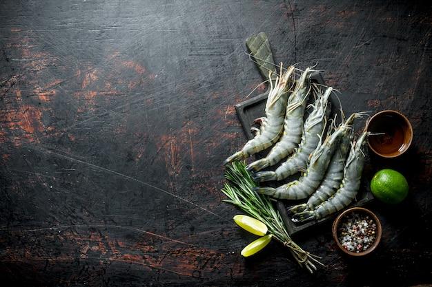 Сырые креветки на разделочной доске с лаймом, розмарином и специями. на темном деревенском