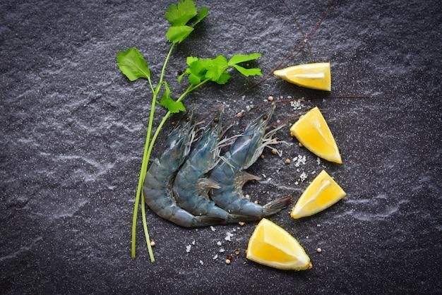Сырые креветки на черной тарелке - свежие креветки креветки для приготовления с лимоном специй на темном фоне в ресторане морепродуктов
