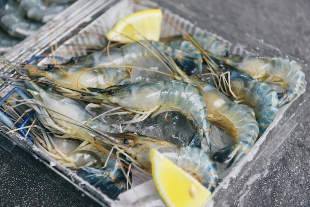 Сырые креветки на льду с лимоном специй на темной тарелке - свежие креветки креветки в коробке в ресторане или на рынке морепродуктов
