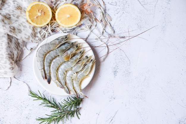 Сырые креветки на белой тарелке с зеленью и лимоном