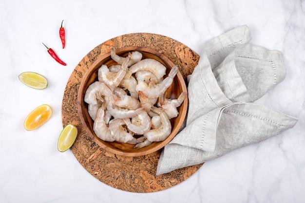 라임과 붉은 고추 요리에 대 한 준비와 함께 나무 접시에 원시 새우 또는 새우.