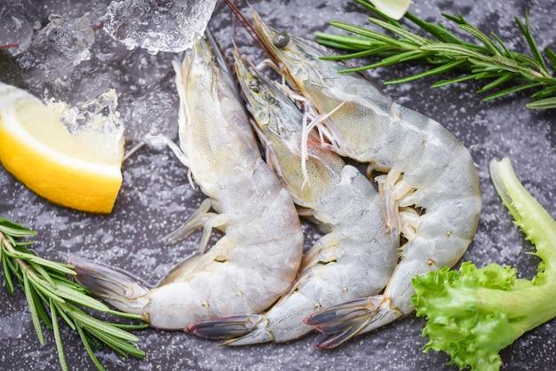Сырые креветки креветки на льду, замороженные в ресторане морепродуктов - свежие креветки на деревянной разделочной доске с травами ингредиентов розмарина и специями для приготовления морепродуктов