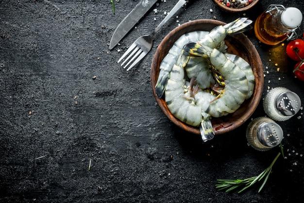 Сырые креветки, сырые со специями. на черном деревенском