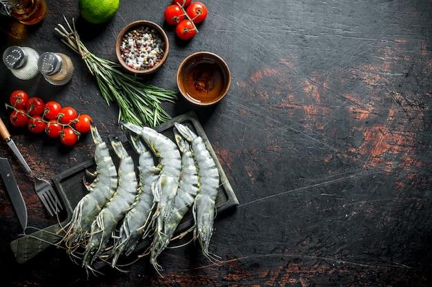 Сырые креветки с помидорами черри, специями и розмарином. на темном деревенском