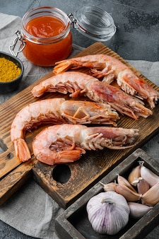 Raw shrimps with garlic, lime , mango sauce and curry for grill set, on gray