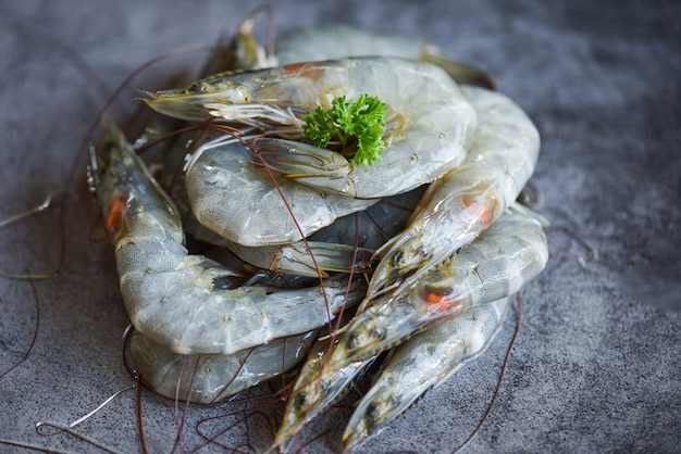 Raw shrimps with herb spices on the dark plate - fresh shrimp prawns at restaurant or seafood market