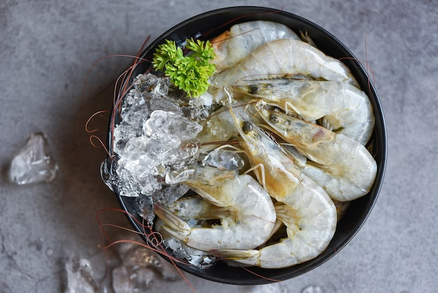 Raw shrimps with ice in bowl