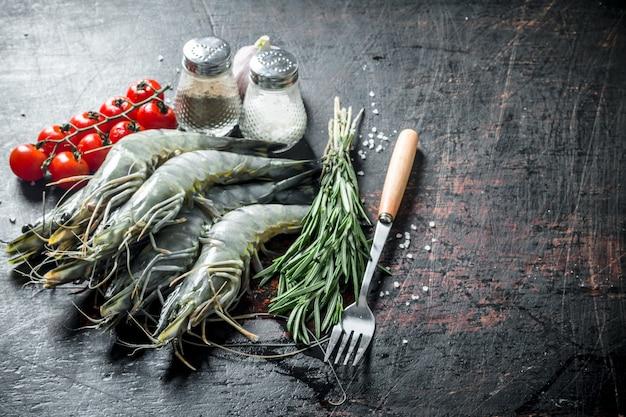 Сырые креветки с розмарином, помидорами и специями.