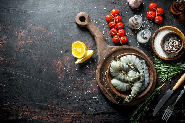 Сырые креветки со специями, помидорами на ветке и розмарином. на темном деревенском