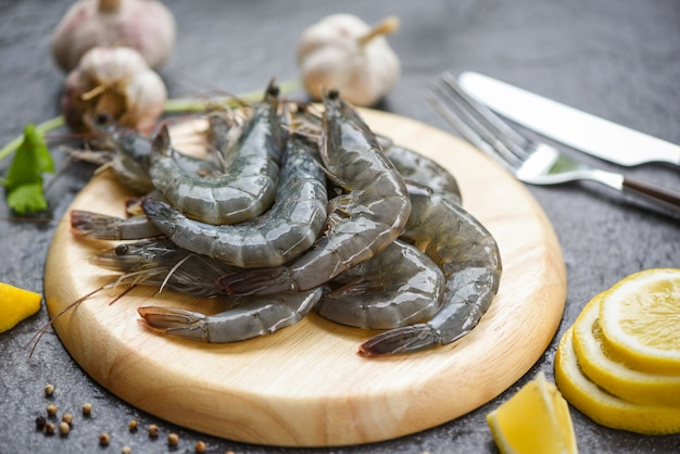 Raw shrimps on wooden cutting board plate fresh shrimp prawns for cooking with spices lemon