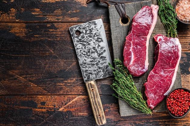 ハーブと木製のまな板の上に生のサーロインビーフミートステーキ