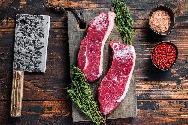 허브와 함께 나무 절단 보드에 원시 등심 쇠고기 고기 스테이크.